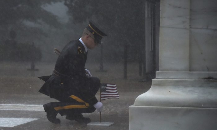 A sentinel endures a severe thunderstorm to place a small American flag at the grave of an unknown soldier. (U.S. Army photo by Sgt. Maryam Treece/3d U.S. Infantry Regiment)