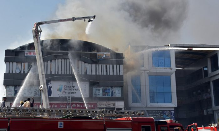 Firefighters douse a fire that broke out in a four-story commercial building in Surat, in the western state of Gujarat, India, May 24, 2019. (Stringer/Reuters)