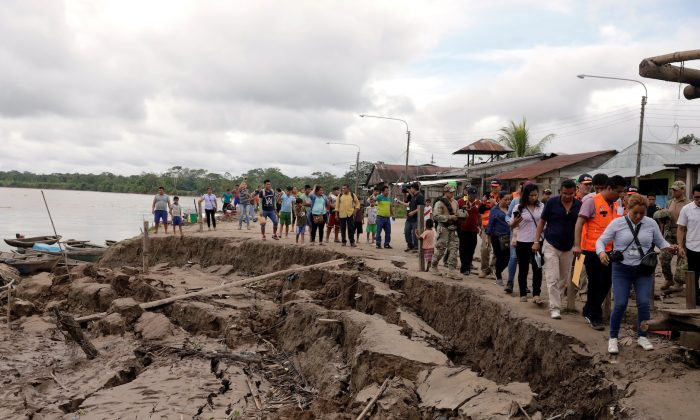 Government officials and media tour an area affected by a quake in Puerto Santa Gema, on the outskirts of Yurimaguas, in the Amazon region, Peru, on May 26, 2019. (Guadalupe Pardo/Reuters)