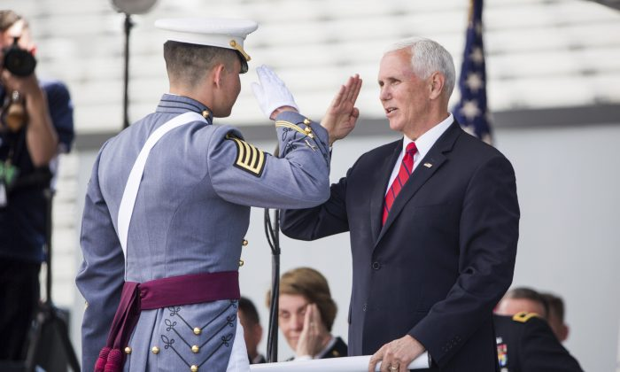 Vice President Mike Pence salutes a graduating cadet before handing him his diploma during graduation ceremonies at the United States Military Academy, in West Point, N.Y., on May 25, 2019. (AP Photo/Julius Constantine Motal)