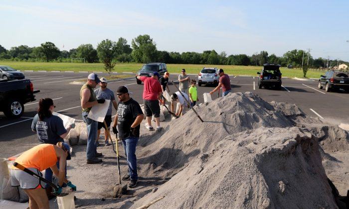 Volunteers fill sand bags for distribution throughout the area for flood prone areas around homes, at the soccer field parking lot in Chaffee Crossing, Ark., on May 25, 2019. Jamie Mitchell/The Southwest Times Record via AP