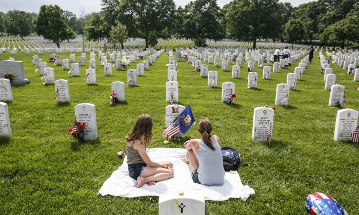 Krista Meinert (R), mother, and Randy Meinert, sister of Jacob Alexander Meinert, LCPL U.S. Marine Corps, sit at his grave in Arlington Cemetery in Arlington, Va., on May 26, 2019. (Samira Bouaou/The Epoch Times)