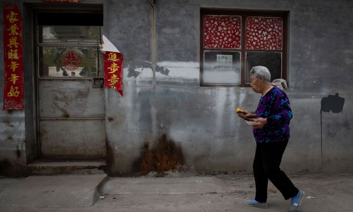 An elderly woman walks on a street while eating and holding a plate with sweet potatoes on the outskirts of Beijing on April 17, 2019. (NICOLAS ASFOURI/AFP/Getty Images)