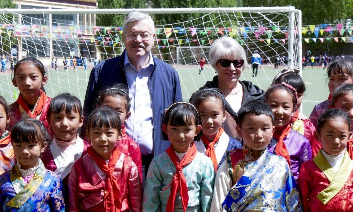 U.S. Ambassador to China Terry Branstad and his wife Christine pose for a group photo with schoolchildren as he visits an elementary school in Lhasa, Tibet on May 22, 2019. (U.S. Mission to China via AP)