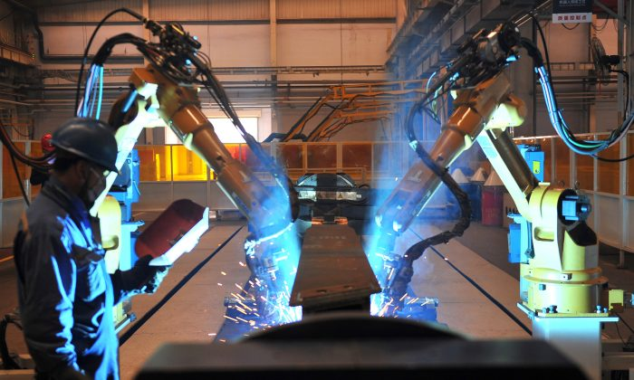 A worker stands next to robotic arms welding pump truck part at a factory of the Foton Loxa Heavy Machinery Co. in Zhangjiakou, Hebei Province, China, on May 24, 2019. (Reuters)