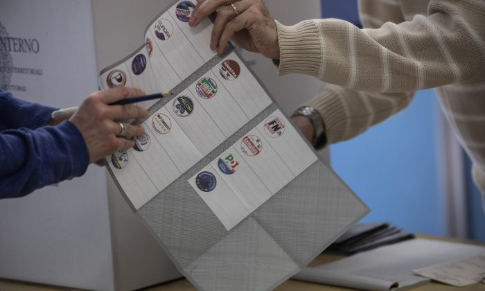 A polling station official gives a ballot to a man during the European Parliamentary election at a polling station in Milan, Italy, on May 26, 2019. (Emanuele Cremaschi/Getty Images)
