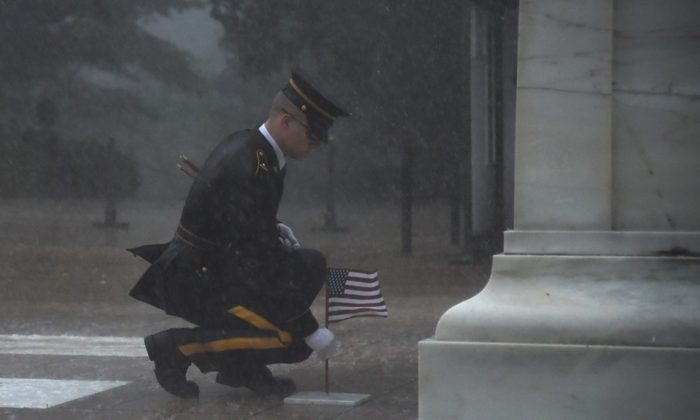 The soldier was seen placing down American flags as winds howled and torrential rain fell in Arlington, Virginia. (3rd U.S. Infantry Regiment)