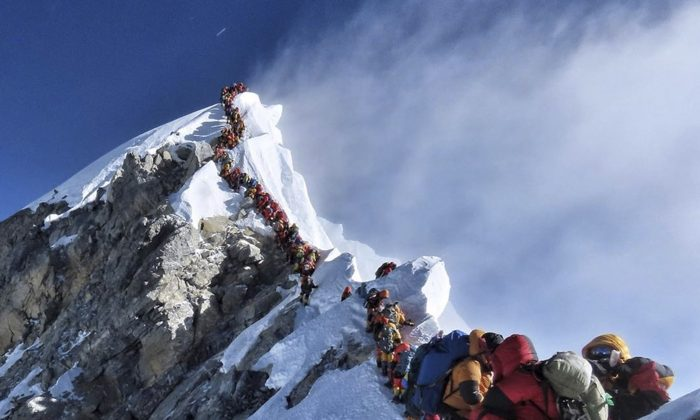 In this photo made on May 22, 2019, a long queue of mountain climbers line a path on Mount Everest. About half a dozen climbers died on Everest last week most while descending from the congested summit during only a few windows of good weather each May. (Nirmal Purja/@Nimsdai Project Possible/The Canadian Press)
