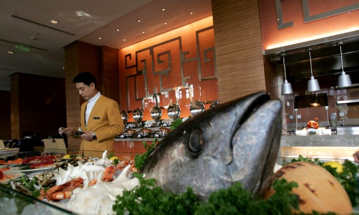 A waiter serves in the coffee bar of an upscale hotel in Beijing, on Feb. 2, 2008. (China Photos/Getty Images)