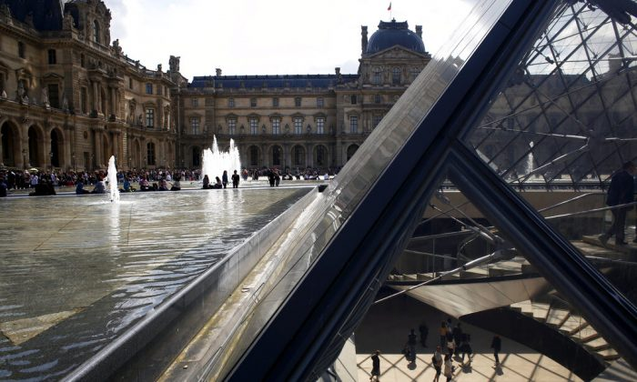 Tourists walk in the pyramid of the Louvre museum as it reopens, Paris, on May 29, 2019. (Thibault Camus/AP Photo)