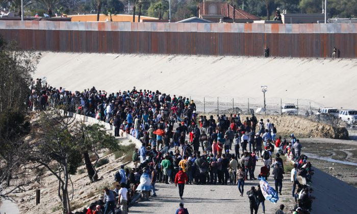 Migrants begin to retreat as U.S. law enforcement uses tear gas to repel their efforts to cross illegally into the United States, just west of the San Ysidro crossing in Tijuana, Mexico, on Nov. 25, 2018. (Charlotte Cuthbertson/The Epoch Times)