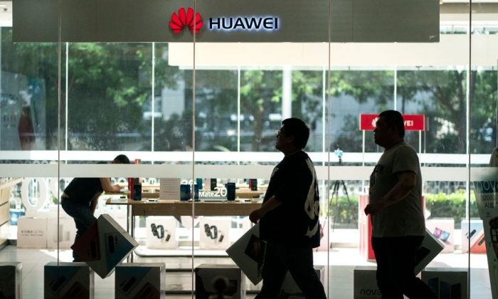 People walk past a Huawei retail store in Beijing on May 23, 2019. (Fred Dufour/AFP/Getty Images)