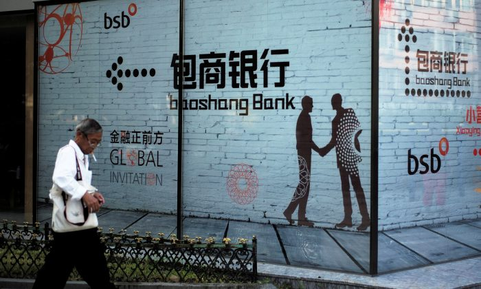 A man walks past a building with an advertisement of Baoshang Bank in Beijing on Sept. 8, 2018. (Reuters)