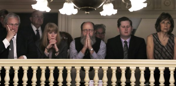 Rob Spencer, center, of Concord, N.H. pauses in prayer
