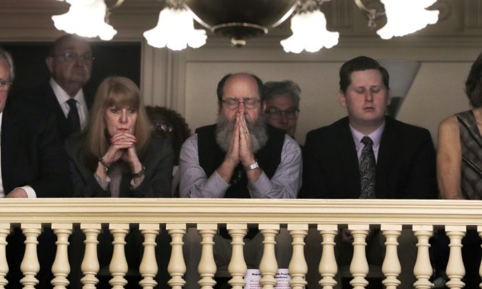 Rob Spencer, center, of Concord, N.H. pauses in prayer as legislators debate prior to a death penalty vote at the State House in Concord, N.H., on May 30, 2019. (Charles Krupa/AP Photo)