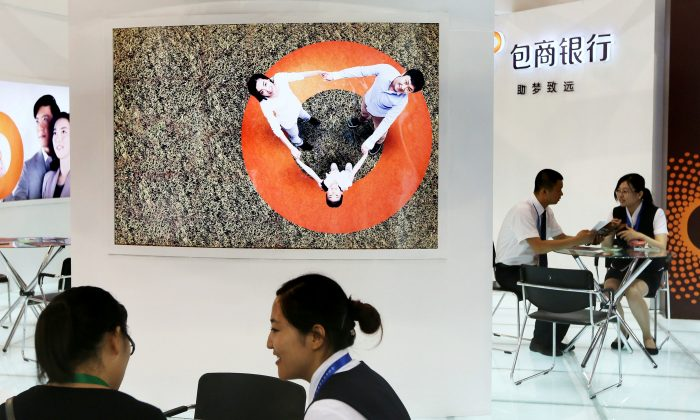 Staff members are seen at the booth of Baoshang Bank at an investment and finance fair for small and medium sized enterprises in Beijing, China on July 18, 2013. (Reuters)