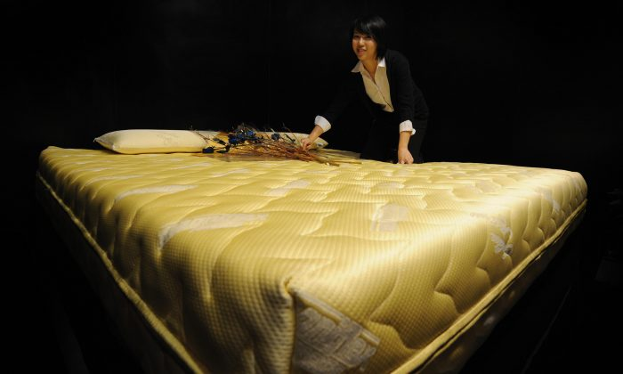 A sales representative shows a $24,000 22-carat gold thread mattress and matching $1,000 22-carat gold thread pillows made by the Italian firm Magniflex at a luxury goods fair in Shanghai, China on Oct. 10, 2008. (Mark Ralston/AFP/Getty Images)