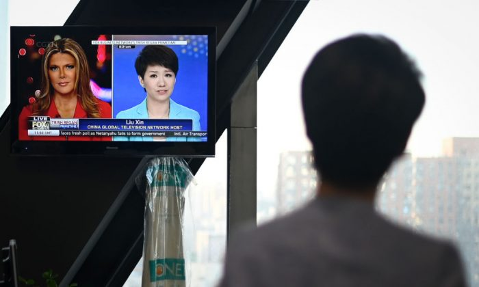 China's state broadcaster CGTN anchor Liu Xin looks at a screen showing her debate with Fox Business Network anchor Trish Regan, at the CCTV headquarters in Beijing on May 30, 2019. (Wang Zhao/AFP/Getty Images)
