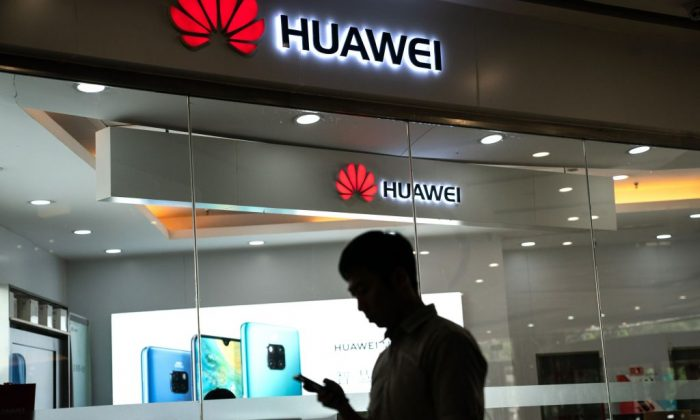 A man walks past a Huawei logo displayed at a retail store in Beijing on May 23, 2019. (Fred Dufour/AFP/Getty Images)