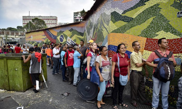People stand in line to receive drums to collect water and water purification tablets from members of the Venezuelan Red Cross in Caracas, Venezuela, on April 16, 2019. (Yuri Corteza/AFP/Getty Images)