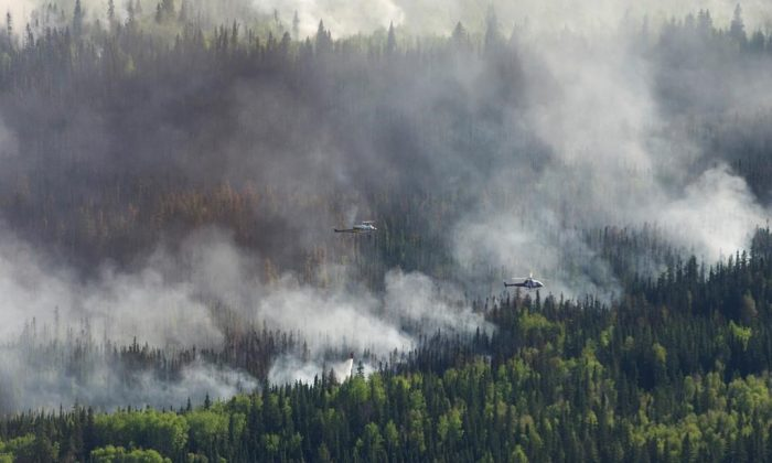 A helicopter drops a bucket of water on the Chuckegg Creek wildfire west of High Level, AB. on May 25, 2019. (Government of Alberta, Chris Schwarz/The Canadian Press)