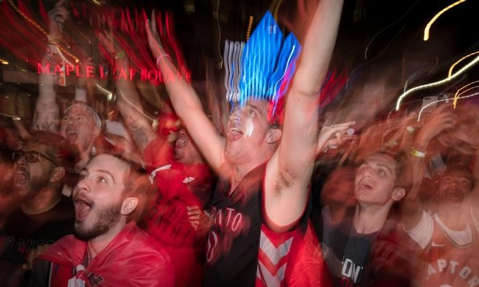 "Toronto Raptors fans celebrate outside the Scotiabank Arena at what's dubbed ""Jurassic Park,"" at the end of their teams NBA finals debut against the Golden State Warriors, winning 118-109, in Toronto on May 30, 2019. (Tijana Martin/The Canadian Press)"