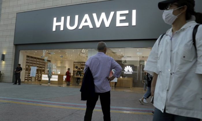 A man stands outside a Huawei store in Beijing on May 20, 2019. (Ng Han Guan/AP)