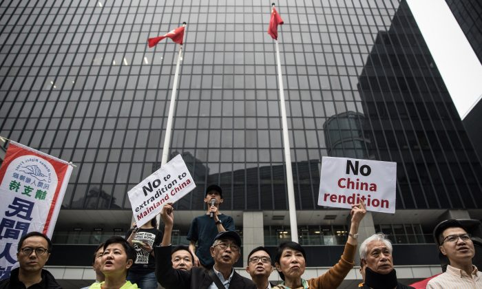 Hong Kong pro-democracy legislator Claudia Mo (center R) and bookseller Lam Wing-kee (center L) display placards outside the government headquarters during a rally in Hong Kong on March 31, 2019 to protest against the government's plans to approve extraditions with mainland China, Taiwan and Macau. (Dale De La Rey/AFP/Getty Images)