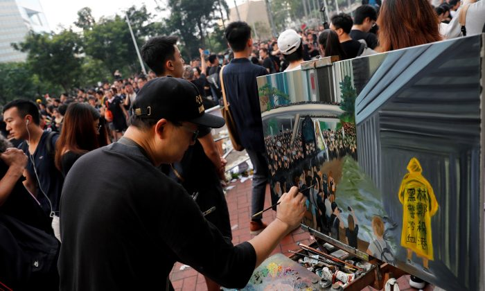Artist Perry Dino paints a scene from protests against the extradition bill, in Hong Kong, on June 16, 2019. (REUTERS/Tyrone Siu)