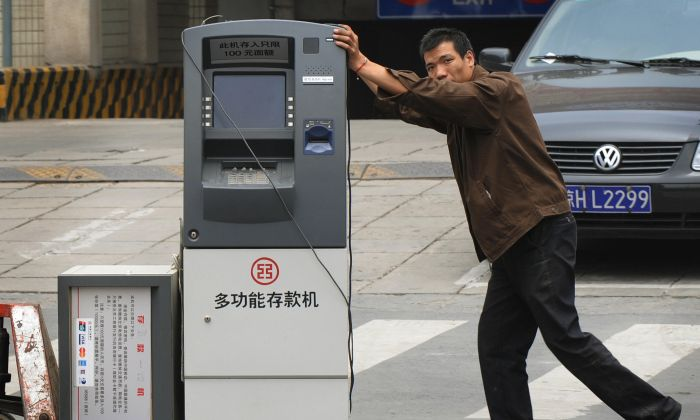 A worker wheels a bank teller machine on the streets of Beijing on June 18, 2008. (MARK RALSTON/AFP/Getty Images)