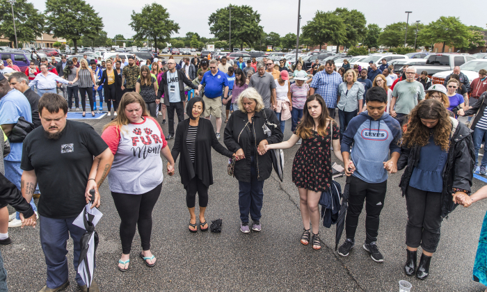 Participants pray together with holding hands during the prayer vigil at Strawbridge Marketplace, Virginia Beach, Va., Saturday, June 1, after the mass shooting, which killed 12 people. (Daniel Sangjib Min/Richmond Times-Dispatch via AP)