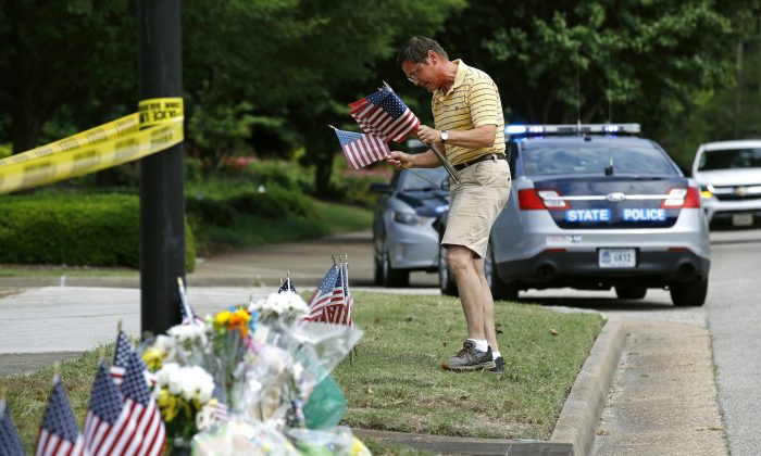 Rich Lindgren places American flags at a makeshift memorial at the edge of a police cordon in front of a municipal building that was the scene of a shooting in Virginia Beach, Va., on June 1, 2019. (Patrick Semansky/AP Photo)