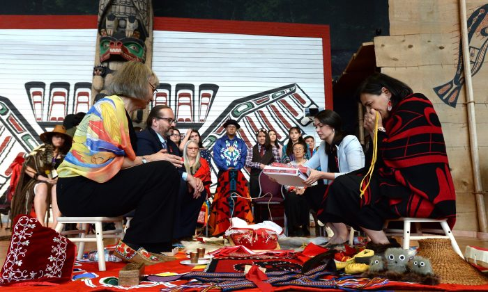Chief commissioner Marion Buller, left to right, and commissioners Brian Eyolfson, Qajaq Robinson and Michele Audette prepare the final report to give to the government at the closing ceremony for the National Inquiry into Missing and Murdered Indigenous Women and Girls in Gatineau, Que., on June 3, 2019. (Adrian Wyld/The Canadian Press)