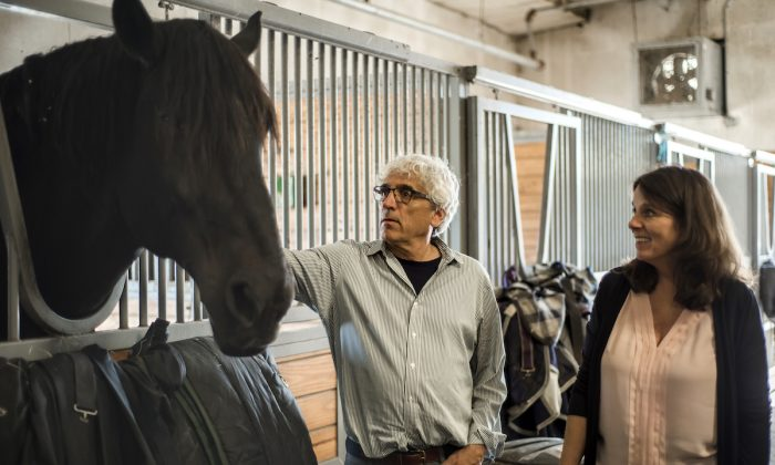 Dr. Yuval Neria (C) with one of the horses at Bergen Equestrian Center. (Courtesy of the Man O' War Project)