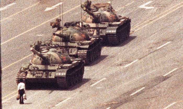 A man stands in front of a column of tanks in the Avenue of Eternal Peace in Beijing on June 5, 1989. (Arthur Tsang/Reuters)
