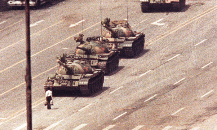 A man stands in front of a convoy of tanks in the Avenue of Eternal Peace in Beijing on June 5, 1989. (Arthur Tsang/Reuters)