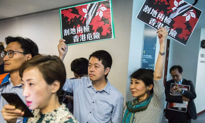 """Pro-democracy lawmakers Ted Hui (C) of the Democratic Party and Claudia Mo (centre R) of the Civic Party hold signs reading """"ceding land with co-location puts Hong Kong in danger"""" at the Legislative Council building in Hong Kong on Aug. 3, 2017. (Isaac Lawrence/AFP/Getty Images)"""