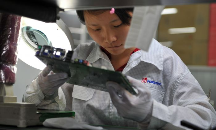 A worker inspects motherboards on a factory line at the Foxconn plant in Shenzhen on May 26, 2010. (VOISHMEL/AFP/Getty Images)