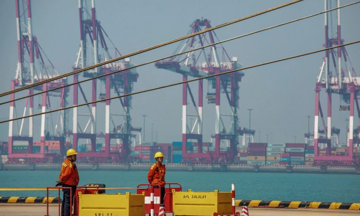 Two staff members stand at a port in Qingdao in China's eastern Shandong Province on April 17, 2019. (STR/AFP/Getty Images)