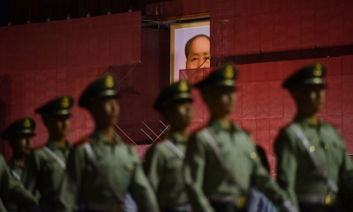 Paramilitary police officers marching past the portrait of late communist leader Mao Zedong on Tiananmen Gate, as it undergoes renovations in Beijing on May 18, 2019. (GREG BAKER/AFP/Getty Images)