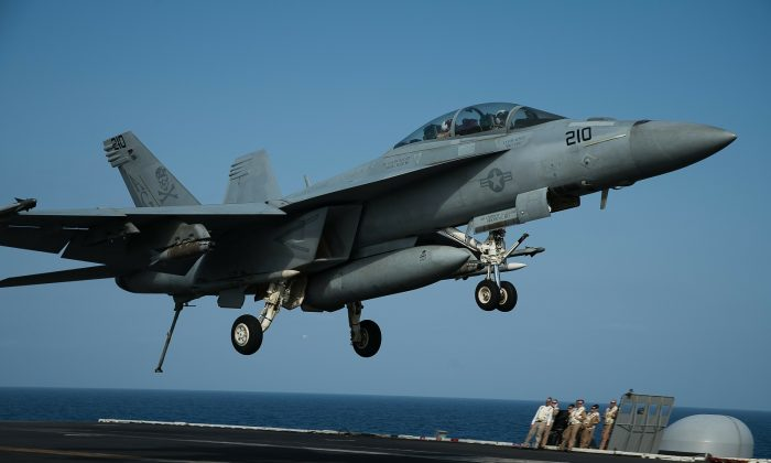An F/A-18 fighter jet lands on the deck of the USS Abraham Lincoln aircraft carrier in the Arabian Sea on June 3, 2019.  AP Photo/Jon Gambrell