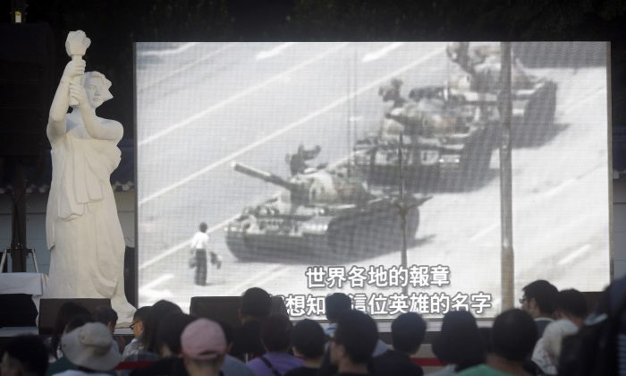 People watch a giant screen as they attend the Tiananmen Anniversary at Democracy Square in Taipei, Taiwan, Tuesday, June 4, 2019, to mark the 30th anniversary of the Chinese military crackdown on the pro-democracy movement in Beijing's Tiananmen Square. (AP Photo/Chiang Ying-ying)