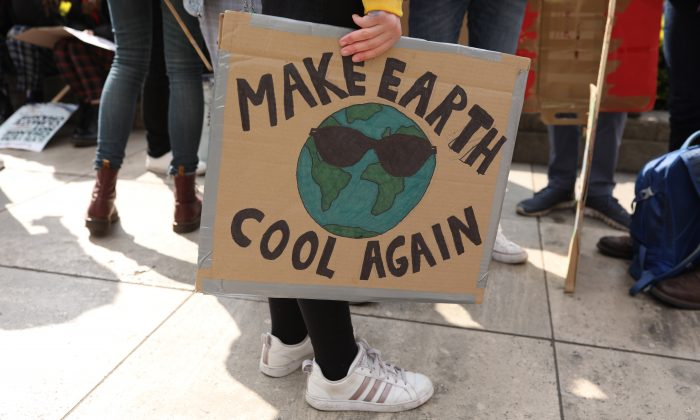 A protester holds a 'Make Earth Cool Again' sign at the YouthStrike4Climate student march in London on April 12, 2019.  Dan Kitwood/Getty Images