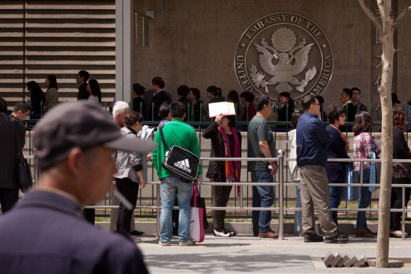 People stand in line outside the visa section of the U.S. embassy in Beijing on April 27, 2012. (Ed Jones/AFP/GettyImages)