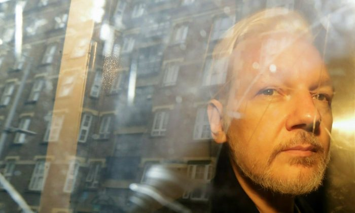 Buildings are reflected in the window as WikiLeaks founder Julian Assange is taken from court, where he appeared on charges of jumping British bail seven years ago, in London on May 1, 2019. (Matt Dunham/AP)