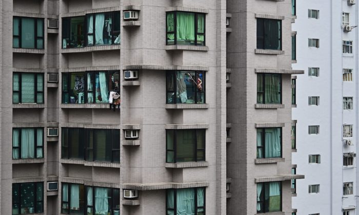 A woman reaching out of a high rise building in China. (Anthony Wallace/AFP/Getty Images)