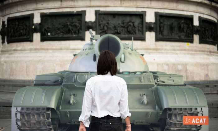 """An activist stands in front of an image of a tank in Paris, France, replicating the scene where an unknown Chinese man, known as the """"Tank Man,"""" stood in front of a column of tanks during the 1989 Tiananmen Square protests in Beijing, to mark the 30th anniversary of the Tiananmen Square massacre on June 4, 2019. (Stringer/AFP/Getty Images)"""