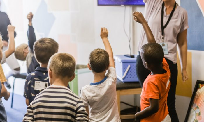 Teacher teaching children raising hands in classroom, (nicolehoneywill/Unsplash)