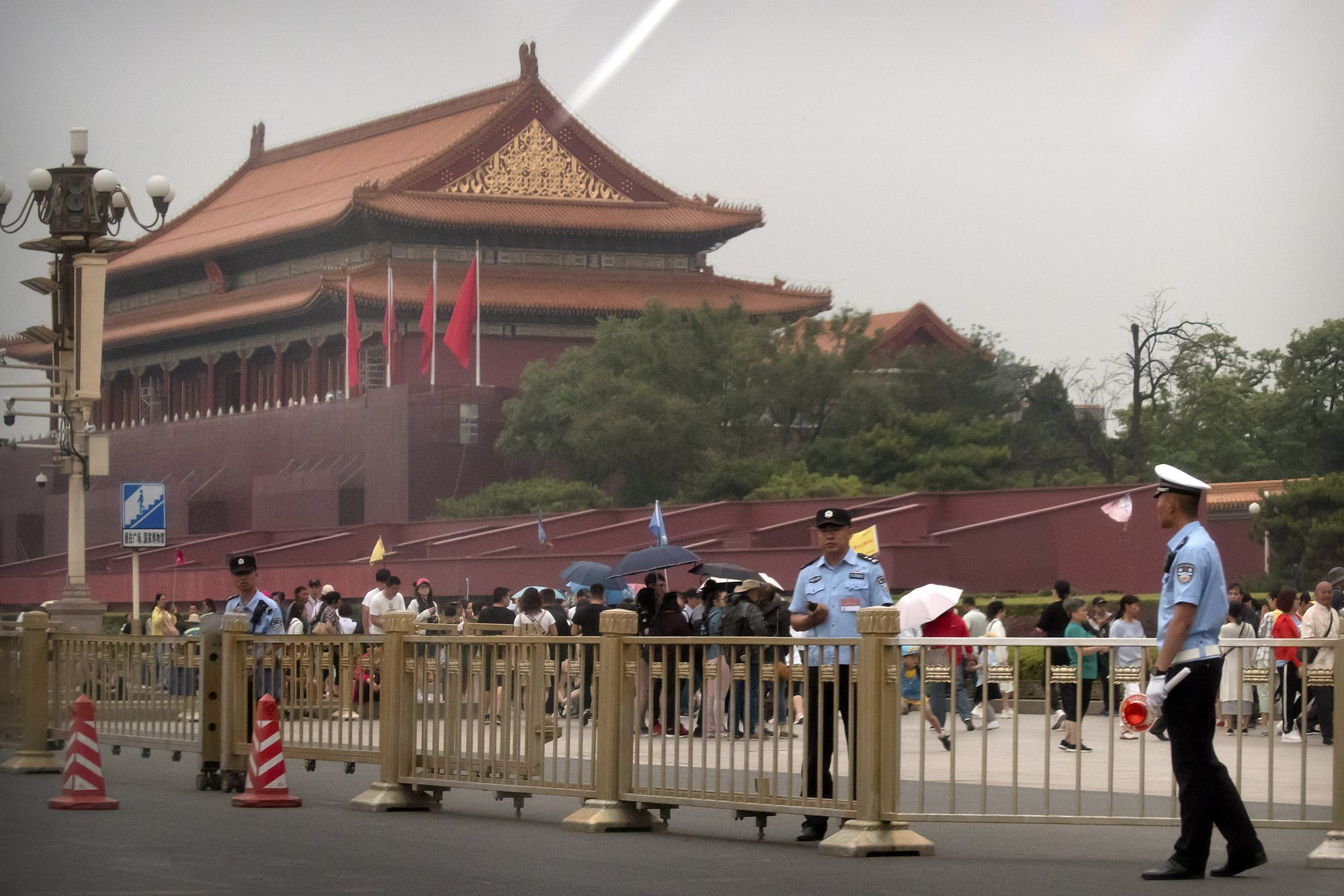 Security officials stand guard in front of Tiananmen Gate next to Tiananmen Square in Beijing on June 4, 2019. (Mark Schiefelbein/AP)