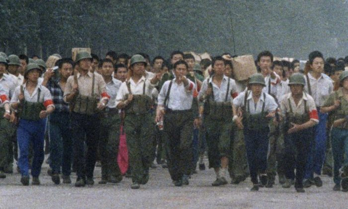 In this June 6, 1989, photo, Chinese soldiers marching away from Tiananmen point out an an Associated Press reporter taking photos, which was against the regulations of martial law that had been declared May 20 and later gave chase, firing twice before the reporter escaped near the International Hotel in Beijing. The Chinese army had fought its way into Tiananmen Square the night of June 3-4 to reclaim the square from student-led demonstrators who had been protesting for democratic reforms for three weeks. (Terril Jones/AP)